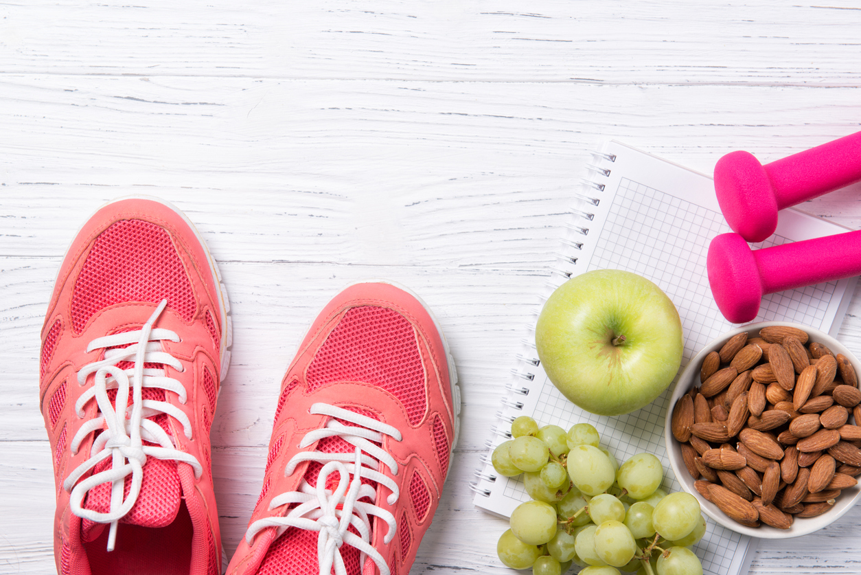 Fitness and healthy eating concept, pink sneakers and dumbbells with apple, grapes and almond nuts on notepad, wooden background, top view with copy space