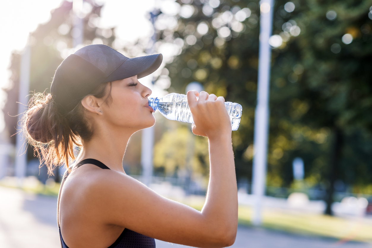 Photo of Sporty young woman drinking water