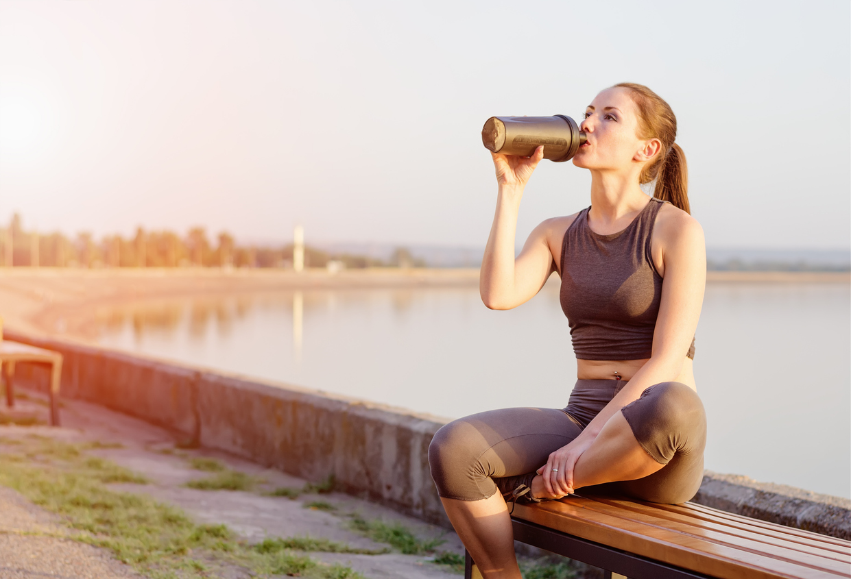 young girl drinks a protein cocktail from a schweeter after jogging